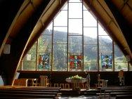 Intérieur de l'Eglise catholique des Diablerets avec cette belle baie vitrée donnant sur la forêt alentour